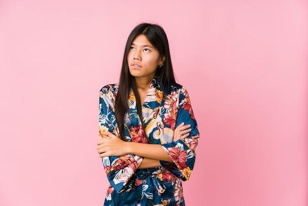 Jovem mulher asiática vestindo um pijama de quimono cansado de uma tarefa repetitiva.