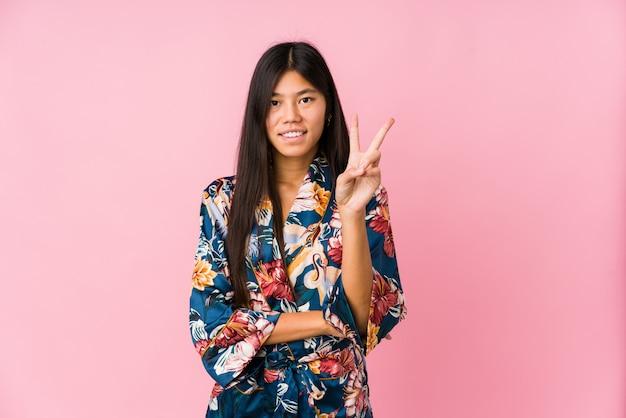 Jovem mulher asiática vestindo um pijama de quimono mostrando o número dois com os dedos.