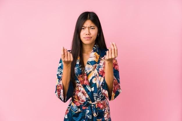 Jovem mulher asiática vestindo um pijama de quimono, mostrando que ela não tem dinheiro.