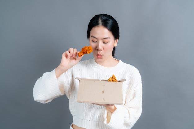 Jovem mulher asiática vestindo um suéter com uma cara feliz e gosta de comer frango frito na parede cinza