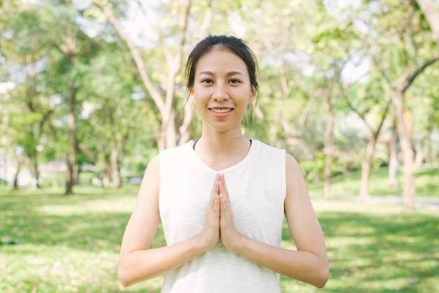 Jovem, mulher asiática, yoga ao ar livre mantenha a calma e medita durante a prática de ioga