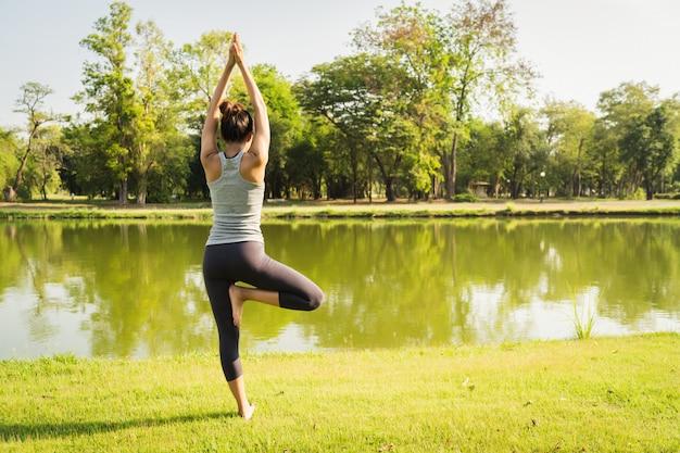 Jovem mulher asiática yoga ao ar livre manter a calma e medita enquanto pratica ioga
