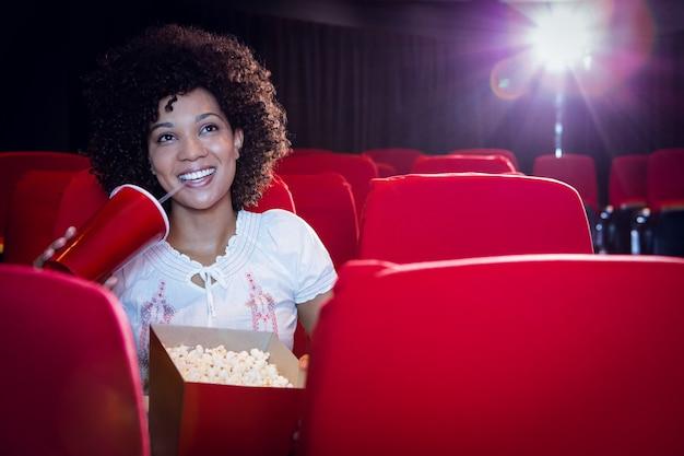 Jovem mulher assistindo a um filme e beber um refrigerante
