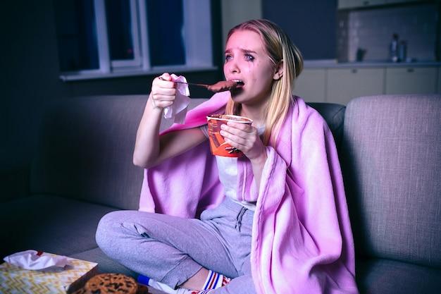Jovem mulher assistindo filme à noite