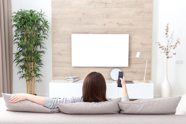 Jovem mulher assistindo tv na sala, tela vazia branca