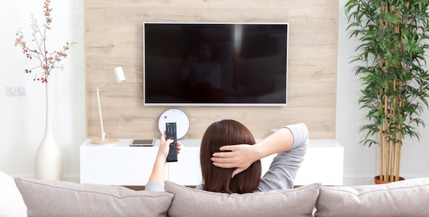 Jovem mulher assistindo tv no quarto