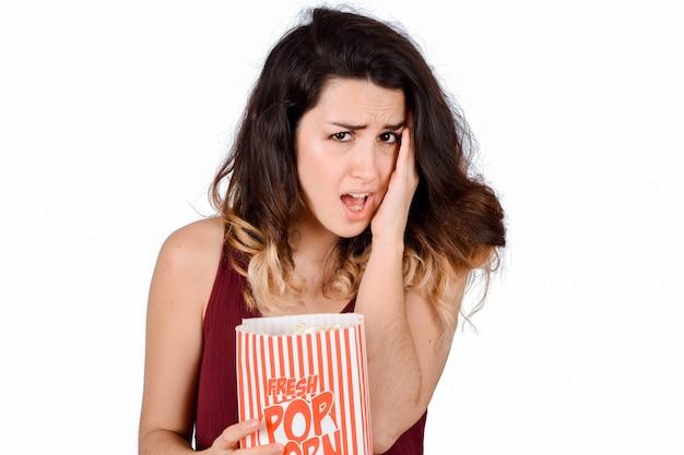 Jovem mulher assistindo um filme de terror e comendo pipoca.