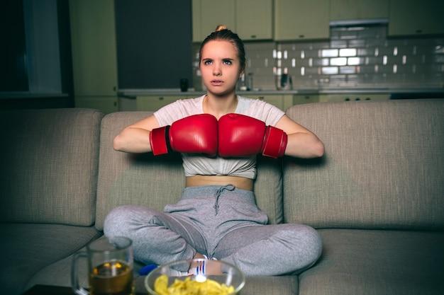 Jovem mulher assistir boxe na tv à noite. sentado com as pernas cruzadas e as mãos em luvas de boxe. sério modelo concentrado ansioso. batatas fritas e cerveja na mesa. sala escura.