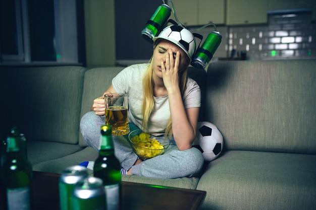 Jovem mulher assistir jogo de futebol na tv à noite.