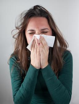 Jovem mulher assoar o nariz com lenço de papel.