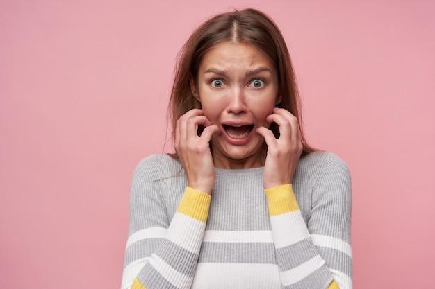 Jovem, mulher assustada com cabelos castanhos compridos. vestindo blusa listrada. tocando seu rosto com medo, horrorizado. assistindo a câmera isolada sobre fundo rosa pastel