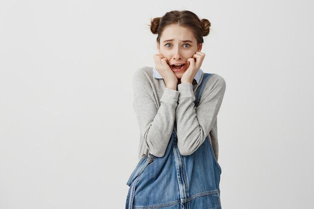 Jovem mulher assustada em casual, segurando as mãos nas bochechas e gritando em pânico. colegial estar apavorada depois de assistir filme de terror. conceito de emoções