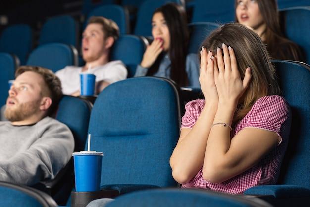 Jovem mulher assustada, escondendo o rosto atrás das mãos em um filme de terror no cinema