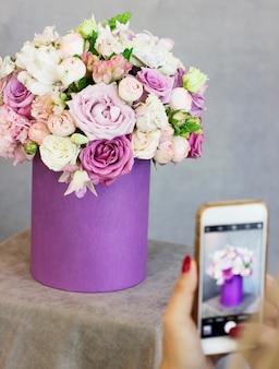 Jovem mulher atirando lindo buquê floral na caixa roxa