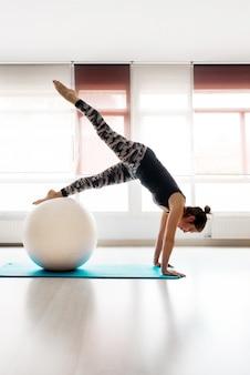 Jovem mulher ativa apoiada no chão com os braços esticados e as pernas apoiadas na bola durante um treino na academia