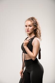 Jovem mulher ativa com agasalho, segurando corda de pular no ombro e olhando para você de pé no cinza