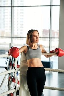 Jovem mulher ativa com luvas de boxe vermelhas, top cinza e perneiras pretas em pé junto às grades do rinque durante o intervalo após o treino