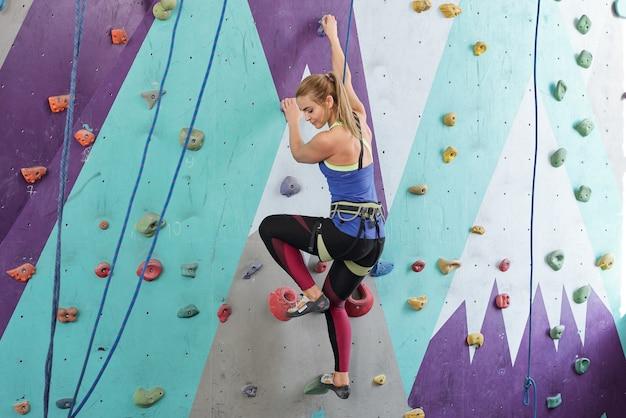 Jovem mulher ativa em roupas esportivas, segurando-se por pedras multicoloridas na parede de escalada, enquanto treinava no lazer