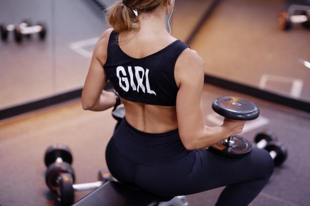 Jovem mulher atlética atraente realiza exercícios com halteres no ginásio