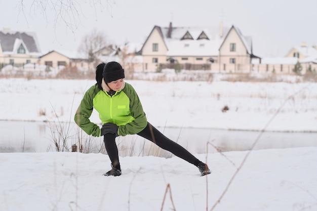 Jovem mulher atlética com uma faixa quente na cabeça, apoiada no joelho e esticando a perna enquanto faz aquecimento no inverno