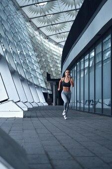 Jovem mulher atlética correndo no estádio urbano da cidade com grandes janelas de espelho no fundo