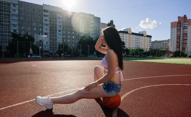 Jovem mulher atlética, de top e moletom, brincando com bola na quadra de basquete ao ar livre.
