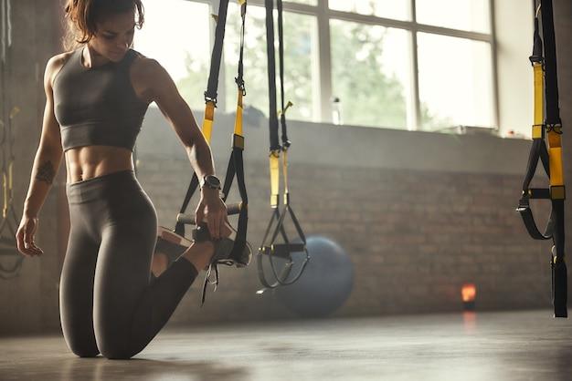 Jovem mulher atlética em roupas esportivas ajustando as alças trx fitness enquanto treinava na academia