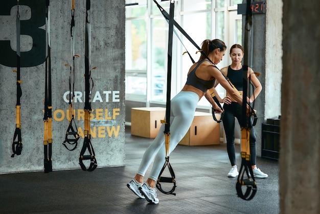 Jovem mulher atlética em roupas esportivas, exercícios com alças trx fitness com personal trainer na academia, fazendo flexões. esporte, treinamento, bem-estar e estilo de vida saudável