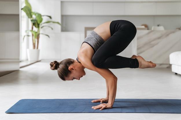 Jovem mulher atlética em roupas esportivas treinando duro com exercícios de ginástica em casa, malhando, fazendo exercícios de equilíbrio no chão