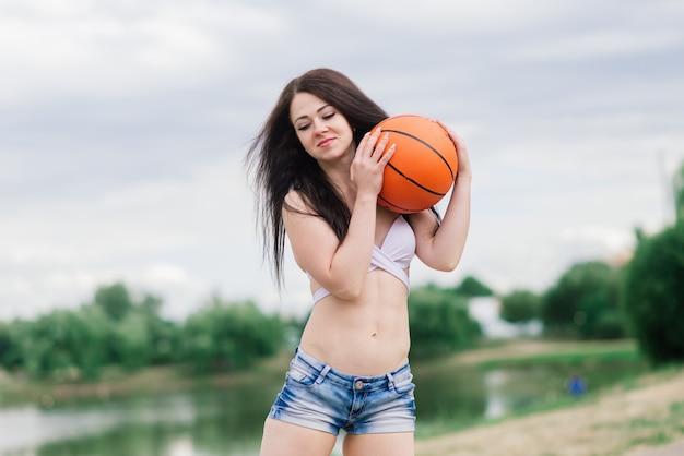 Jovem mulher atlética, em um top e calça de moletom, jogando com bola na quadra de basquete ao ar livre.