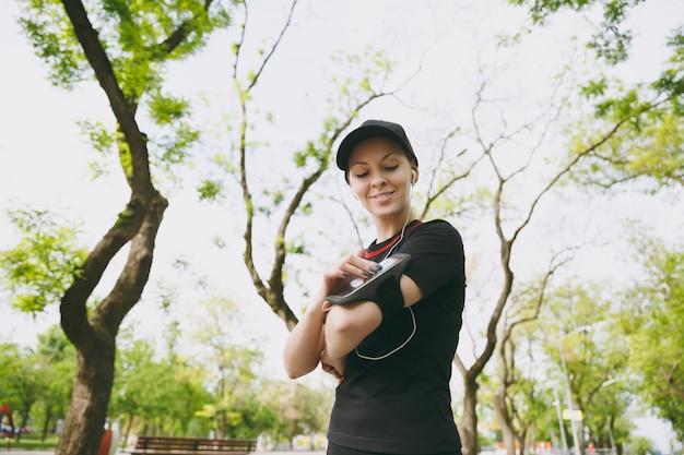 Jovem mulher atlética em uniforme preto com fones de ouvido, ouvindo música, olhando no celular usando o aplicativo, app para correr ou correr, treinar no parque da cidade ao ar livre