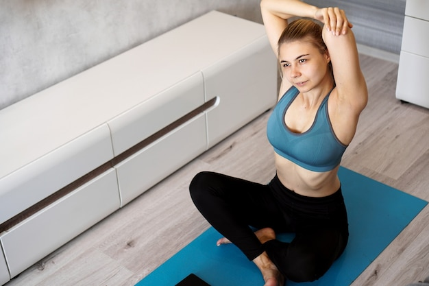 Jovem mulher atlética fazendo alongamento antes do treino em casa. instrutor de fitness em casa