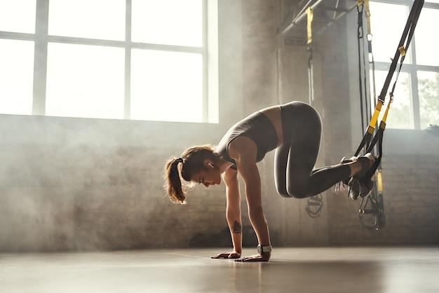 Jovem mulher atlética fazendo exercícios trx em roupas esportivas, treinando pernas com alças trx fitness