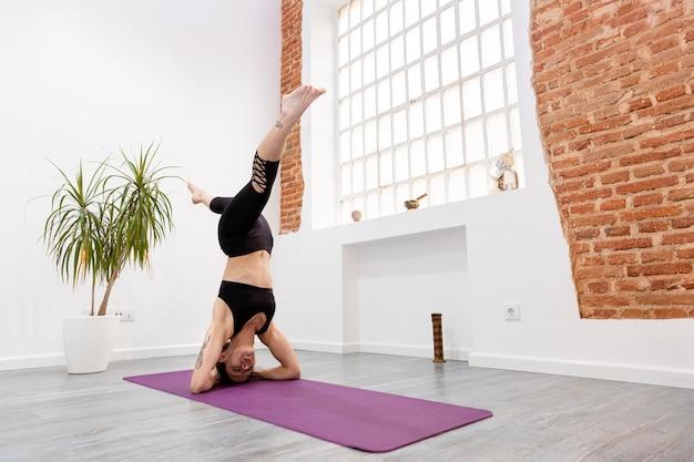 Jovem mulher atlética fazendo parada de mãos em casa. conceito de pilates, ioga, fitness e treinamento. espaço para texto.