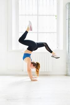 Jovem mulher atlética malhando fazendo parada de mãos em uma academia equilibrando com pernas abertas