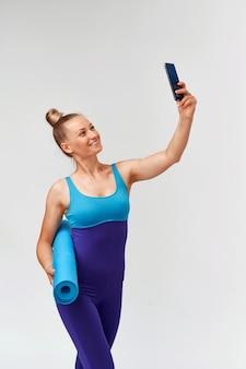 Jovem mulher atlética no sportswear com uma esteira de ginástica nas mãos