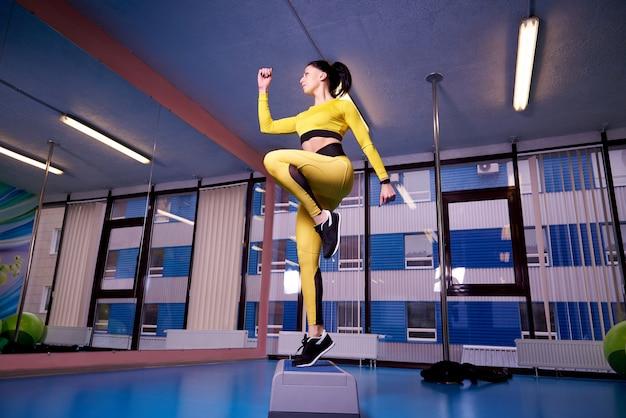 Jovem mulher atlética que usa a plataforma da etapa no gym.