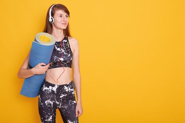 Jovem mulher atlética usando fones de ouvido e sportswear preto segurando o tapete de ioga azul