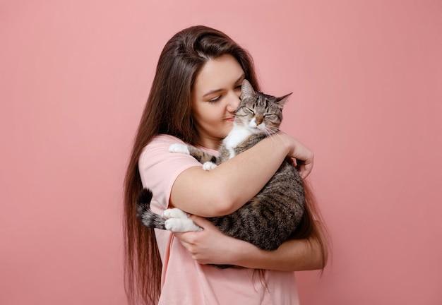 Jovem mulher atraente abraçando o gato nas mãos, fundo rosa, menina beijando o gato
