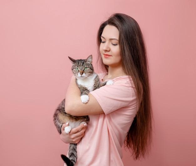 Jovem mulher atraente, abraçando o gato nas mãos