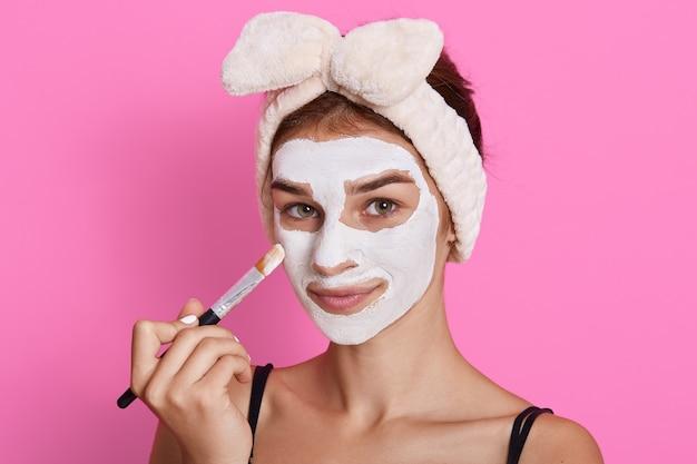 Jovem mulher atraente aplica escova de sagacidade de máscara branca, olhando para a câmera, waring hairband com laço isolado sobre fundo rosa, procedimentos de beleza na manhã.