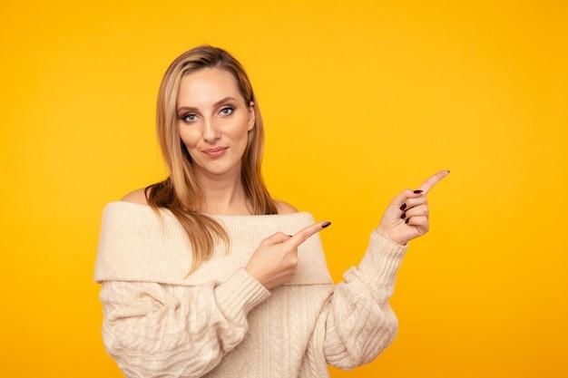 Jovem mulher atraente apontando por dedos isolados.