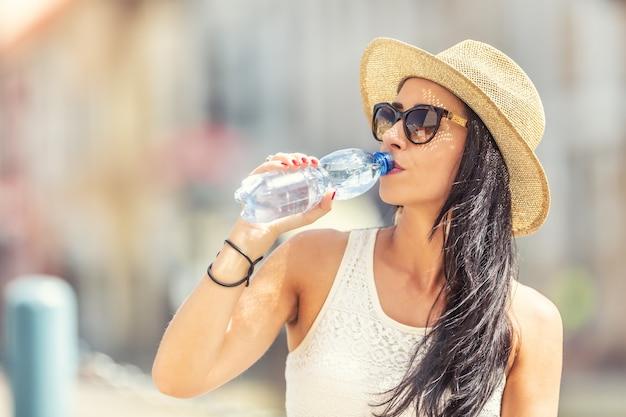 Jovem mulher atraente bebe água limpa durante um dia quente de verão.
