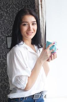 Jovem mulher atraente, bebendo chá ou café em sua cozinha. lady indors relaxante com copo de bebida quente
