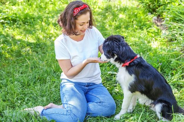 Jovem mulher atraente brincando com um filhote de cachorro fofo border collie no jardim de verão ou no parque da cidade ao ar livre