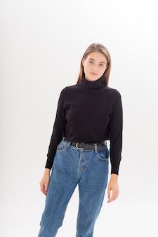Jovem mulher atraente caucasiana com cabelo comprido e calça jeans preta de gola alta