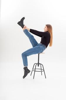 Jovem mulher atraente caucasiana com gola alta preta, jeans azul calça as botas