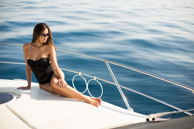 Jovem mulher atraente coloca no iate de luxo flutuando no mar