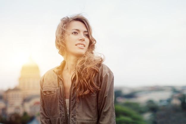 Jovem mulher atraente com bom humor, apreciando a bela paisagem da cidade