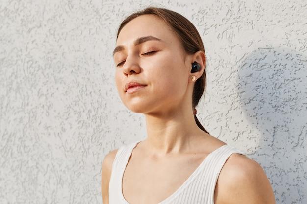 Jovem mulher atraente com cabelo escuro, blusa branca, ouvindo música, usando airpods, mantendo os olhos fechados, curtindo a música favorita durante o treino ao ar livre.